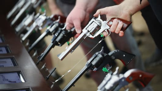 Gun enthusiasts look over Ruger pistols at the NRA Annual Meetings & Exhibits on May 21, 2016 in Louisville, Kentucky.