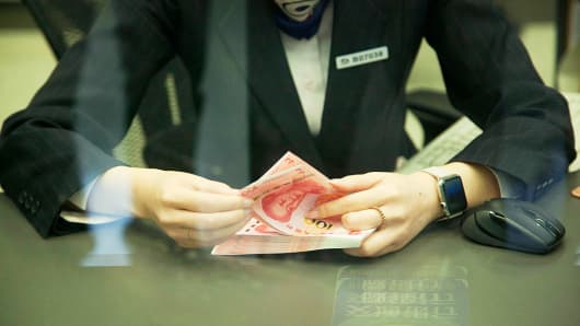 A bank staff member counts new 100 yuan notes on November 12, 2015 in Beijing, China.