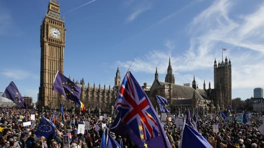 Demonstrators holding EU and Union flags gather in front of the Houses of Parliament in Parliament Square following an anti Brexit, pro-European Union march in London on March 25, 2017, ahead of the British government's planned triggering of Article 50.