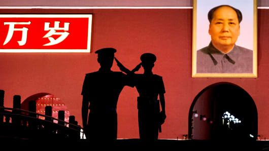 Chinese Paramilitary police officers salute each other as they stand guard below a portrait of the late leader Mao Zedong in Tiananmen Square in Beijing, China.