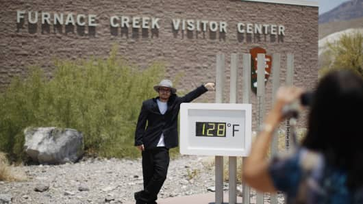 A tourist from California poses for a snapshot by an unofficial thermometer reading at Furnace Creek Visitor Center reading 128 degrees.