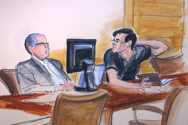 Martin Shkreli seated with book speaking to his attorney Marc Agnifilo in court during jury deliberations.