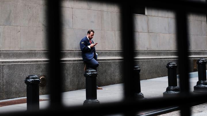 A trader stands outside of the New York Stock Exchange (NYSE) on July 25, 2017 in New York City.