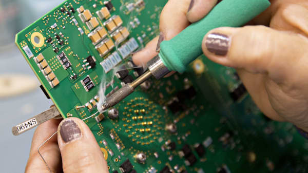 A worker solders a component to a circuit board used in a liquid crystal display (LCD) screen for Boeing Co. aircraft at the Rockwell Collins Inc. production facility in Manchester, Iowa, U.S., on Wednesday, Aug. 31, 2016.
