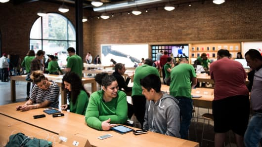 Employees help customers at the Apple Williamsburg store in the Brooklyn, New York on Friday, May 20, 2017.