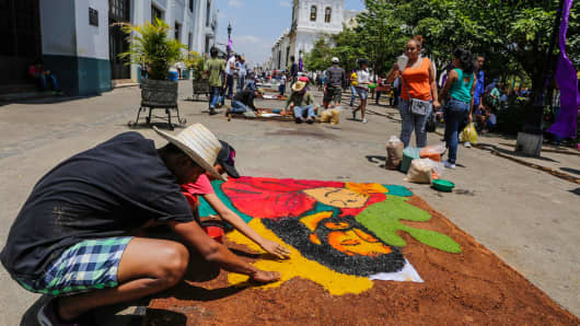 People participate in a sawdust carpets contest during the celebration of the Holy Week in front of the cathedral in Leon, on April 10, 2017.