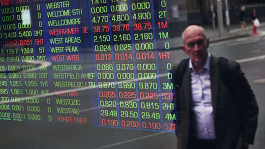 A pedestrian walks past the display at the Australian Securities Exchange (ASX) in Sydney on September 30, 2015.