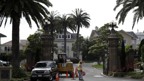 A construction workers stands in front of a gate leading into the Presidio Terrace neighborhood Monday, Aug. 7, 2017, in San Francisco. Thanks to a city auction stemming from an unpaid tax bill, a Bay Area real state investor bought the street in the neighborhood and now owns th