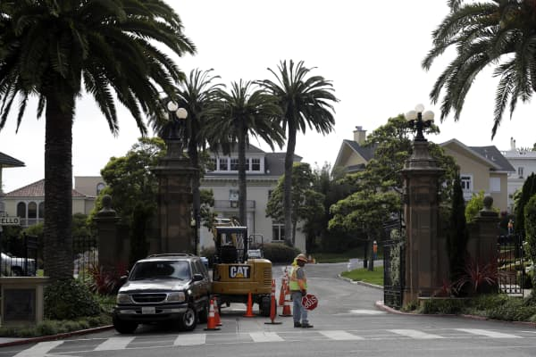 "A construction workers stands in front of a gate leading into the Presidio Terrace neighborhood Monday, Aug. 7, 2017, in San Francisco. Thanks to a city auction stemming from an unpaid tax bill, a Bay Area real state investor bought the street in the neighborhood and now owns the sidewalks, the street itself and other areas of ""common ground"" in the private development that, the San Francisco Chronicle reports, has been managed by the homeowners association since at least 1905."