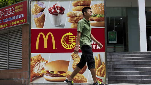 A pedestrian walks past an advertisement for McDonald's in Shenzhen, China, on August 4, 2014.