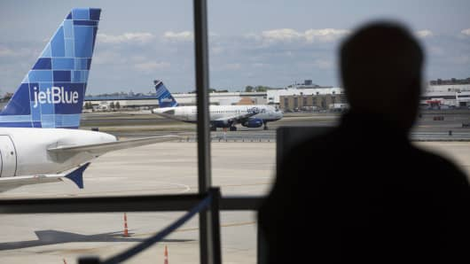 A JetBlue Airways Corp. plane moves on the tarmac as a passenger waits in Terminal 5 at John F. Kennedy International Airport (JFK) airport in New York.
