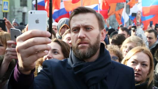 Russian opposition leader Alexei Navalny (C) takes a selfie photo during a mass march marking the one-year anniversary of the killing of opposition leader Boris Nemtsov on February 27, 2016 in Moscow, Russia.