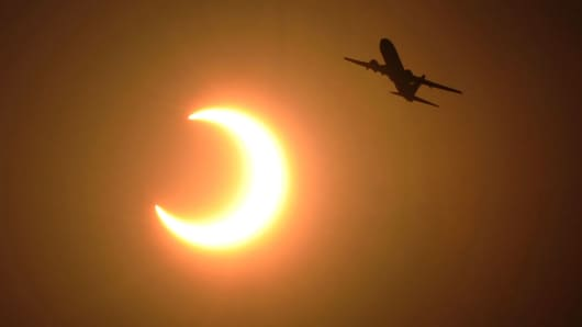 A file photo of a plane flying in front of a partial solar eclipse.