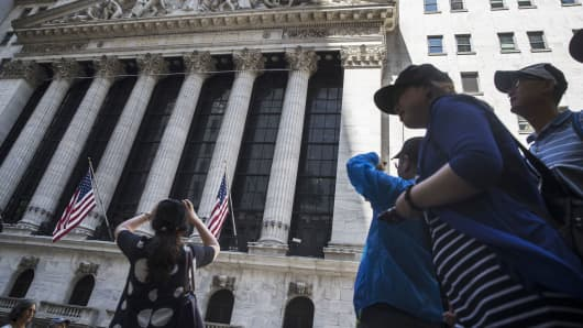 A person takes a photograph of the New York Stock Exchange.