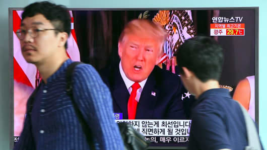People walk past a television screen showing US President Donald Trump at a railway station in Seoul on August 9, 2017.