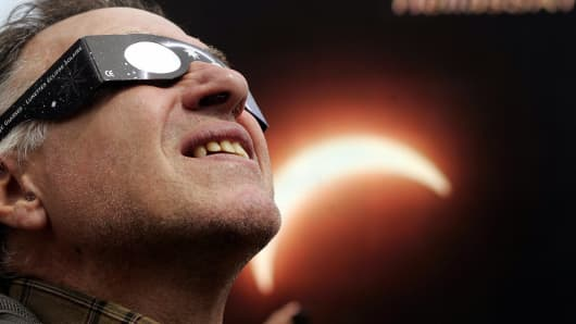 A man looks at the sun through a special glasses at a central Athens square during the partial solar eclipse.