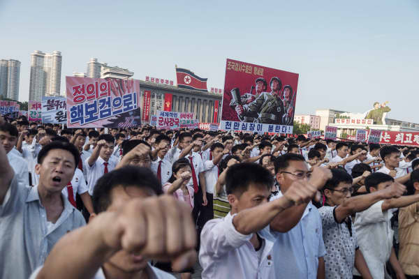 People wave banners and shout slogans as they attend a rally in support of North Korea's stance against the US, on Kim Il-Sung square in Pyongyang on August 9, 2017.