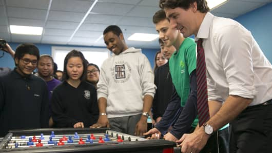 Prime Minister Justin Trudeau plays a game of foosball with high school students.