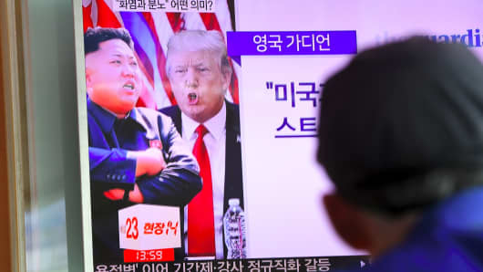 A man watches a television news programme showing US President Donald Trump (C) and North Korean leader Kim Jong-Un (L) at a railway station in Seoul on August 9, 2017.