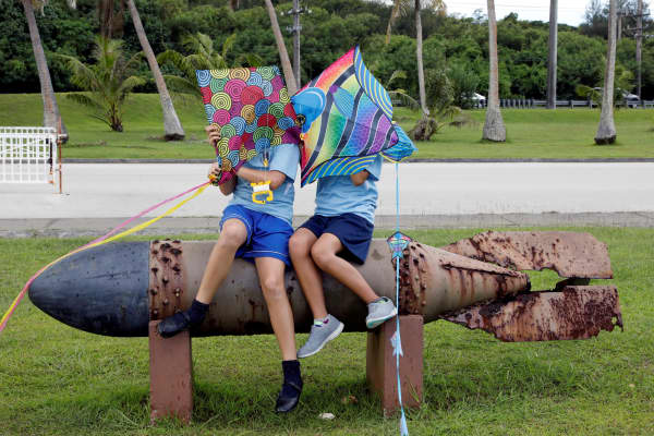 Students sit on the World War II remnants of a torpedo at Asan Memorial Park on the island of Guam, a U.S. Pacific Territory, August 11, 2017.