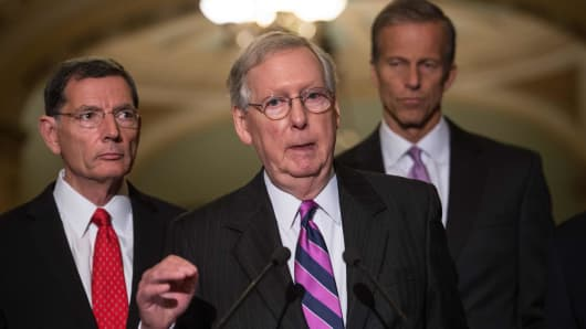 Senate Majority Leader Mitch McConnell speaks to the press with senators John Barasso (L) of Wyoming and John Thune (R) of South Dakota after the Republican senators' weekly lunch at the US Capitol in Washington, DC, on August 1, 2017.