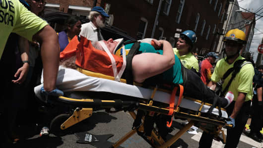 "Rescue workers transport a victim who was injured when a car drove through a group of counter protesters at the ""Unite the Right"" rally Charlottesville, Virginia, U.S., August 12, 2017."