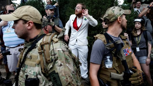 White nationalists stand behind militia members in Charlottesville.