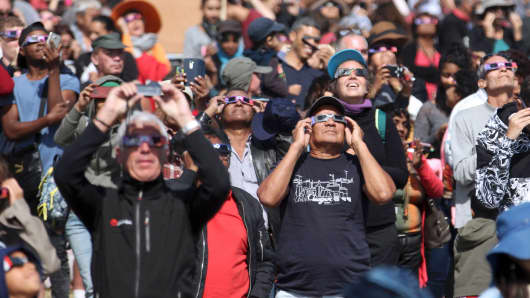 People look through eclipse viewing glasses, telescopes or photo cameras an annular solar eclipse.