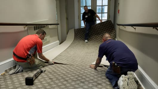 Construction workers lay carpet on a ramp from the West Wing offices to the White House colonnade.