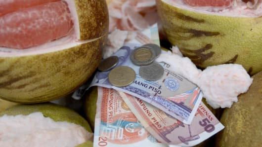 Philippine peso bills and coins are laid on basket as a street vendor peels a fruit in Manila