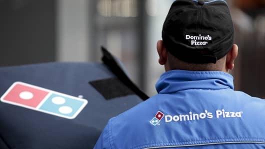 The Domino's Pizza company logo is displayed on the jacket of delivery driver in London, U.K., on February 27, 2017.