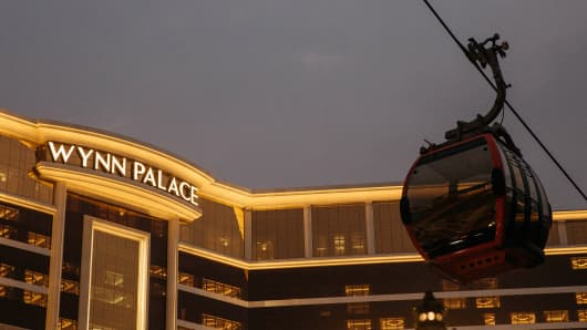 A SkyCab cable car travels past Wynn Resorts Ltd.'s Wynn Palace casino resort at night in Macau, China.