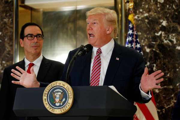 "President Donald Trump answers questions about his responses to the deaths and injuries at the ""Unite the Right"" rally in Charlottesville as he talks to the media with Treasury Secretary Steven Mnuchin (L) at his side in the lobby of Trump Tower in New York, August 15, 2017."