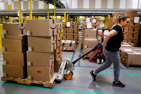 An employee pulls a cart stacked with boxes at the Amazon.com fulfillment center in Kenosha, Wisconsin.