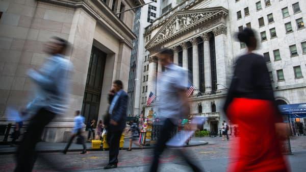 Pedestrians walk along Wall Street near the New York Stock Exchange in New York.