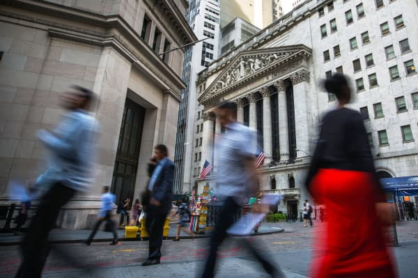 Pedestrians walk along Wall Street near the New York Stock Exchange in New York.