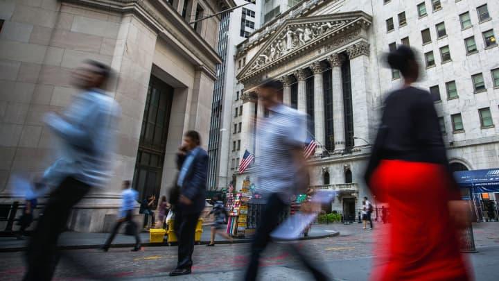 Pedestrians walk along Wall Street near the New York Stock Exchange in New York, Aug. 14, 2017.