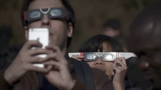 People use protective glasses and mobile phones to watch a partial solar eclipse.