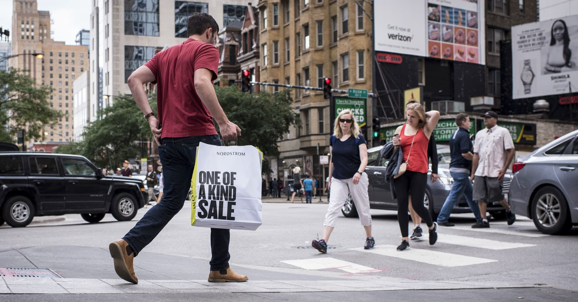 A shopper carries a Nordstrom bag while crossing a street in downtown Chicago.