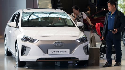 Visitors look at a Hyundai Ioniq electric vehicle at the Hyundai Motorstudio showroom in Goyang, South Korea, on Friday, July 14, 2017.