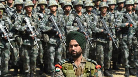 Happier times: An Indian Army soldier stands in front of a group of People's Liberation Army troops during joint drills last year.