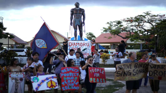 Protesters hold signs during a People for Peace Rally at the Chief Quipuha Statue on August 14, 2017 in Hagatna, Guam.