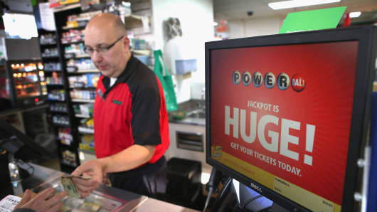 A store clerk sells a Powerball lottery ticket at his 7-Eleven store in Chicago, Illinois.