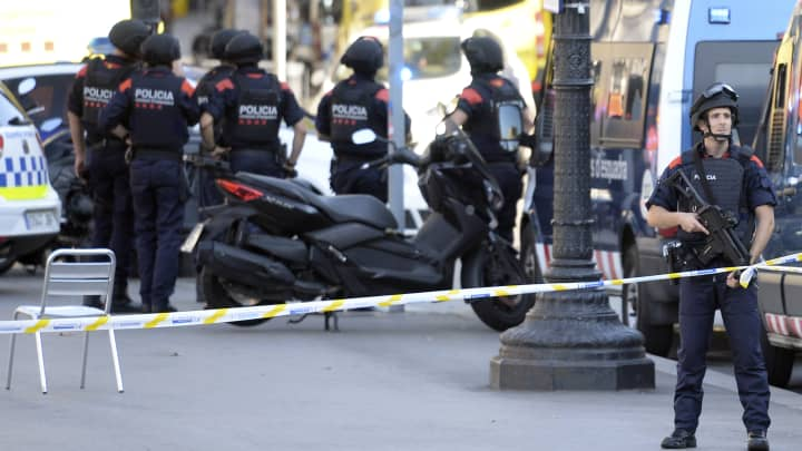 Armed policemen stand in a cordoned off area after a van ploughed into the crowd, injuring several persons on the Rambla in Barcelona on August 17, 2017.