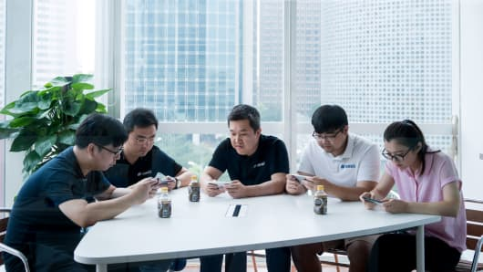 Co-workers play Honor of Kings, the biggest moneymaking smartphone game in the world, on their lunch break in Beijing, Aug. 15, 2017.