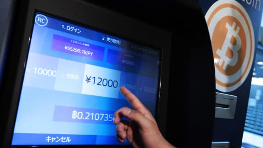 Eugene Aono, a spokesperson for BMEX bitcoin exchange, demonstrates usage of the company's Robocoin-branded automated teller machine (ATM) at The Pink Cow restaurant and bar in Tokyo, Japan