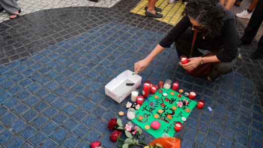 A woman lights a candle next to first flowers and a message to the victims on August 18, 2017 in Barcelona