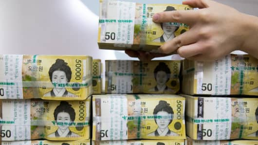 An employee arranges genuine bundles of South Korean 50,000 won banknotes at the Counterfeit Notes Response Center of KEB Hana Bank in Seoul, South Korea.