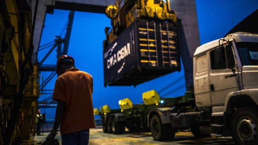 A worker waits as a shipping container is unloaded from the Hapag-Lloyd Holding AG Prague Express cargo ship onto a truck at the Cia Siderurgica Nacional SA (CSN) Sepetiba Tecon terminal inside the Port of Itaguai in Rio de Janeiro, Brazil.