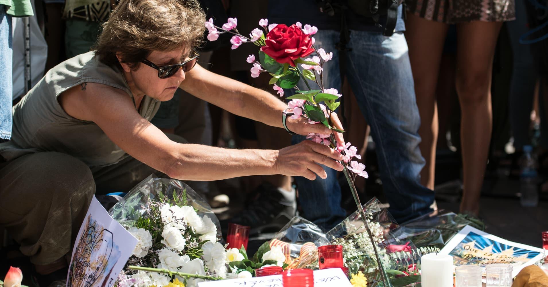 A woman lays a flower on Las Ramblas near the scene yesterday's terrorist attack, on August 18, 2017 in Barcelona, Spain.